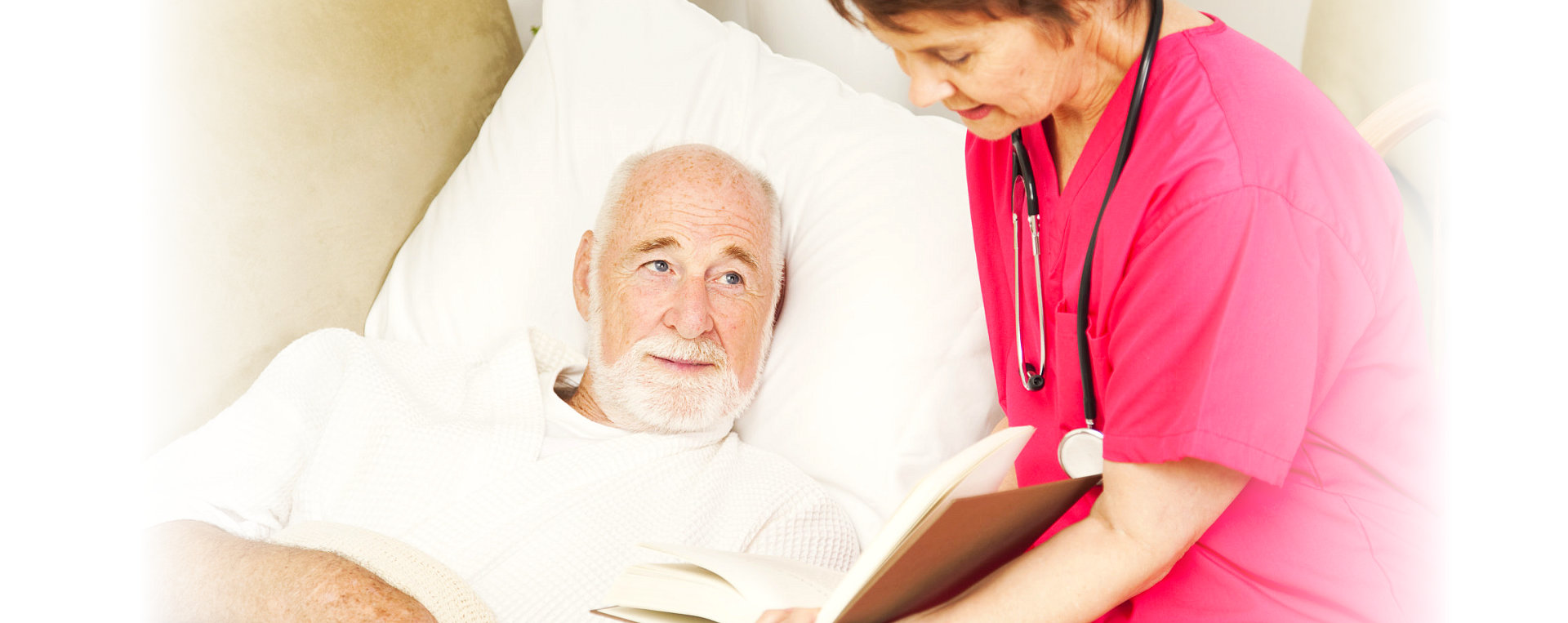 Friendly home caregiver reads to an elderly patient