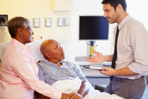 doctor talking to senior couple on ward holding clipboard